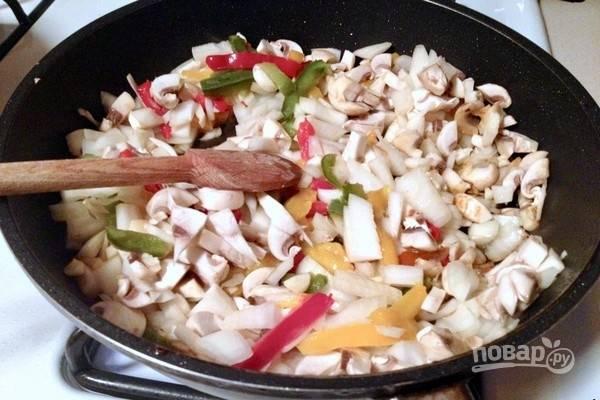 Переложите обжаренную свинину на тарелку, а в сковороду положите все овощи и обжарьте их в течение нескольких минут до прозрачности.