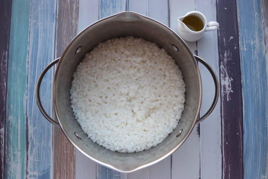 В первую очередь приготовьте рис. Рис нужно несколько раз промыть в холодной воде. Затем залить 250 мл холодной воды, довести до кипения, перемешать и варить под крышкой до готовности. Готовому рису дайте постоять под крышкой 15 минут, посолите и заправьте кунжутным маслом.