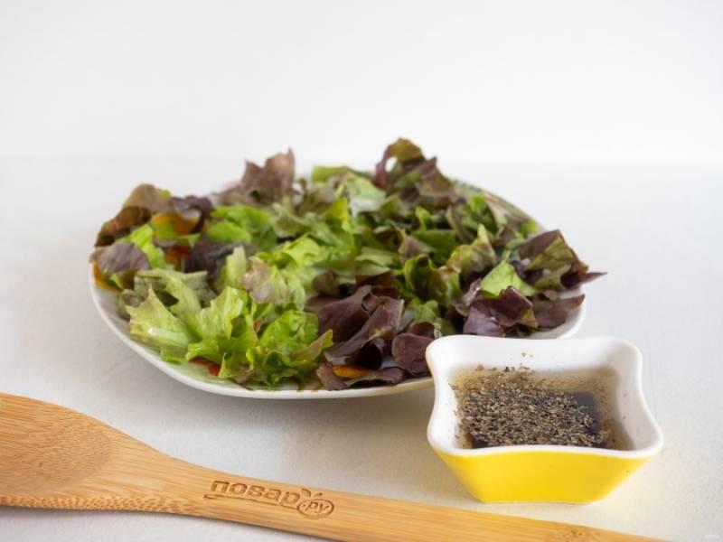 Приготовьте соус. Перемешайте оливковое масло, бальзамический соус, мед и  итальянские травы. Полейте 1/3 соуса листья салата.