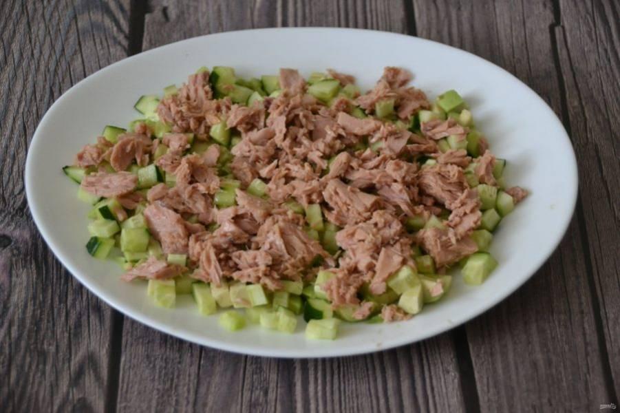 Выложите тунец поверх огурца и авокадо.