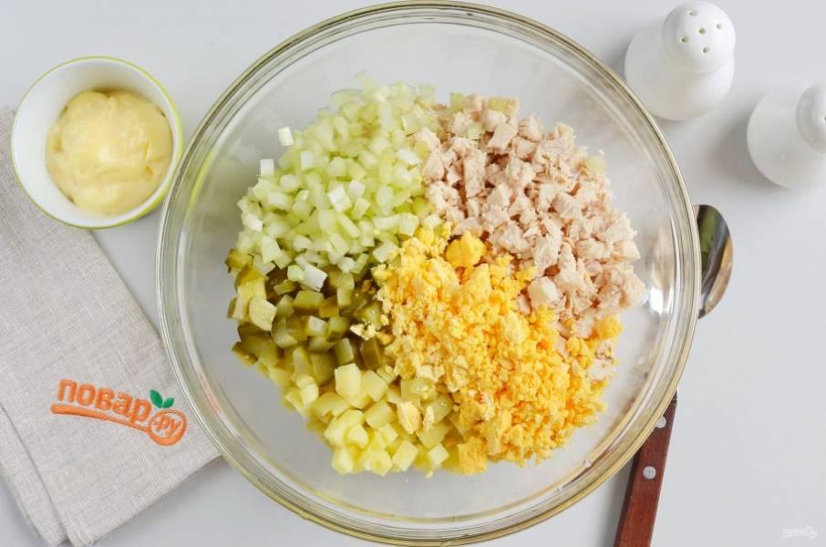 В большой миске смешайте нарезанные кубиками картофель, курицу, сельдерей, огурец, желтки.