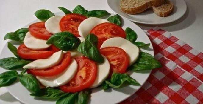 Выкладываем листья базилика на тарелку, по краю. По центру, чередуя, выкладываем кружочки помидоров и сыра.