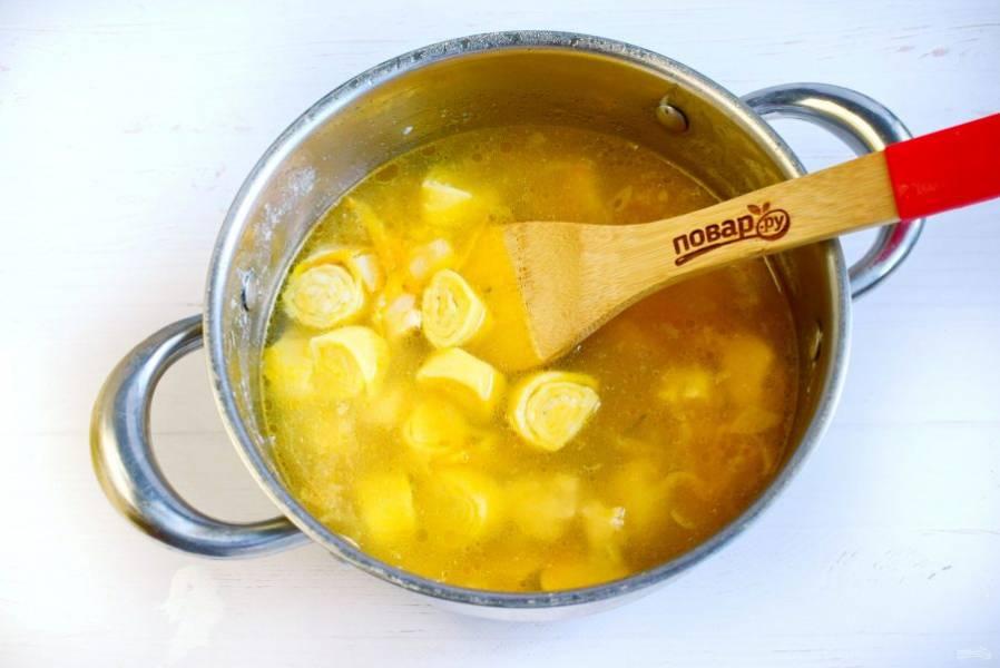 Отправляйте рулетики в суп по одному, перемешайте аккуратно, доведите до кипения, варите на медленном огне в течение 5 минут. Добавьте соль по вкусу, рубленную зелень, дайте настояться 15 минут.