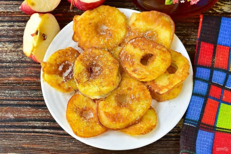 Выложите яблочные донатсы на блюдо. Сверху посыпьте их дополнительно сахаром и корицей. Подайте их к столу.