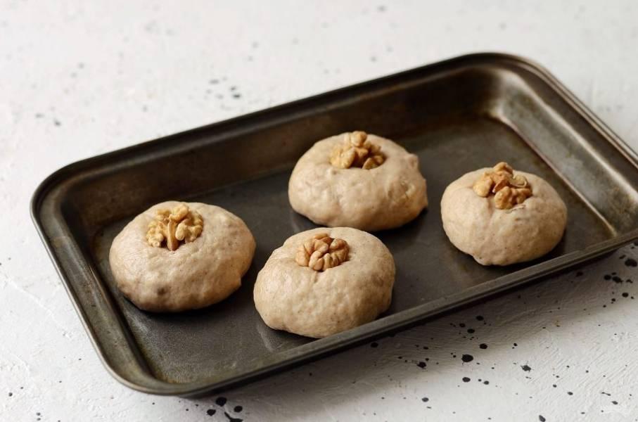 Сформируйте из теста булочки, сверху можно украсить их орехами. Выпекайте булочки в заранее разогретой до 190 градусов духовке 15 минут.