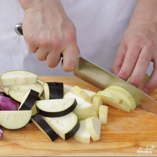 Помыть и очистить овощи. Луковицу разрезаем на 8 частей, чеснок мелко рубим, кабачок и баклажан нарезаем полукругами толщиной 1-2 см, перцы - крупными кусками, помидоры - кубиками.