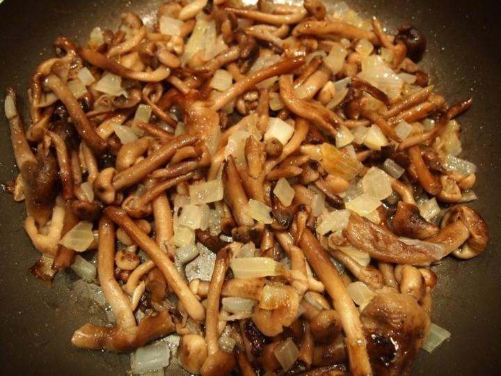 1. Для начала необходимо очистить и нарезать мелкими кубиками луковицу. Отправить на сковороду с разогретым маслом лук и обжарить до слегка золотистого цвета. Затем добавить на сковороду грибы, предварительно слив маринад, и обжарить с луком около 3-5 минут.