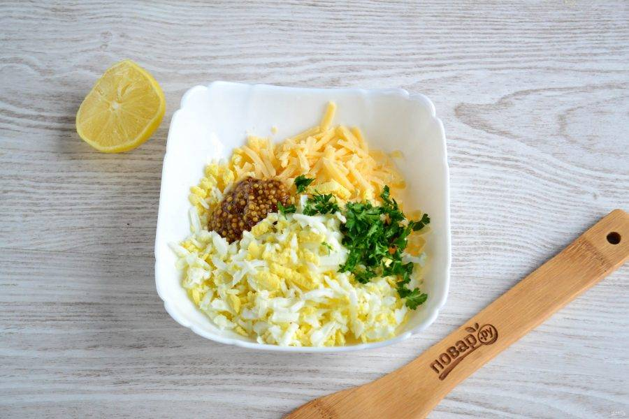 Яйца и твердый сыр натрите на крупной терке, мелко нарежьте петрушку, добавьте горчицу и немного лимонного сока.