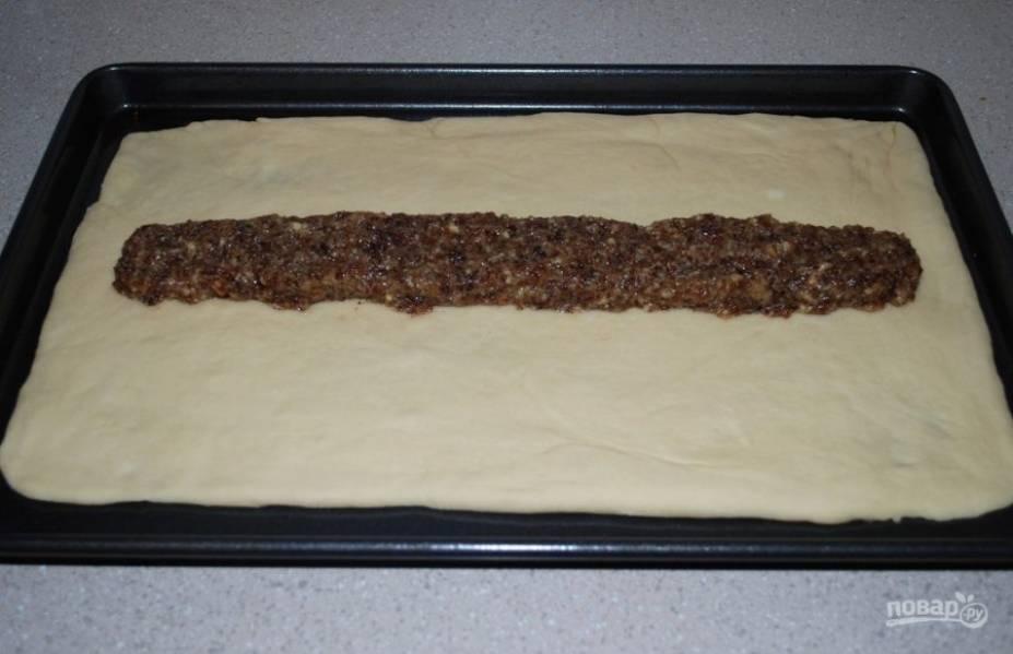 3. В отдельной миске смешайте измельченный чернослив и грецкие орехи, цедру, мускатный орех, 2 столовые ложки сливочного масла и 2 столовые ложки сахара. Разместите тесто на противень для выпекания и в середину вдоль положите приготовленную начинку из чернослива.