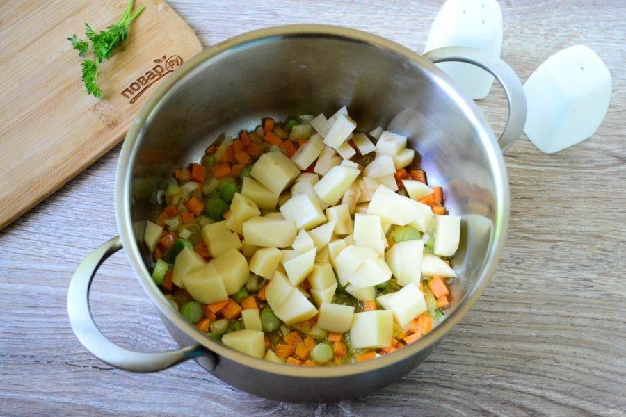 Картофель порежьте на небольшие куски и тоже отправьте в кастрюлю, жарьте несколько минут.