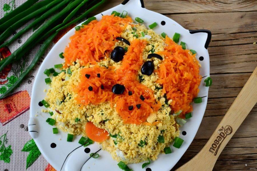 И последний штрих - декор. Желтки растолките в крошку, морковь натрите на мелкой терке. Из моркови сделайте уши и нос, все остальное пространство заполните желтком. С помощью маслин сделайте глазки и носик.