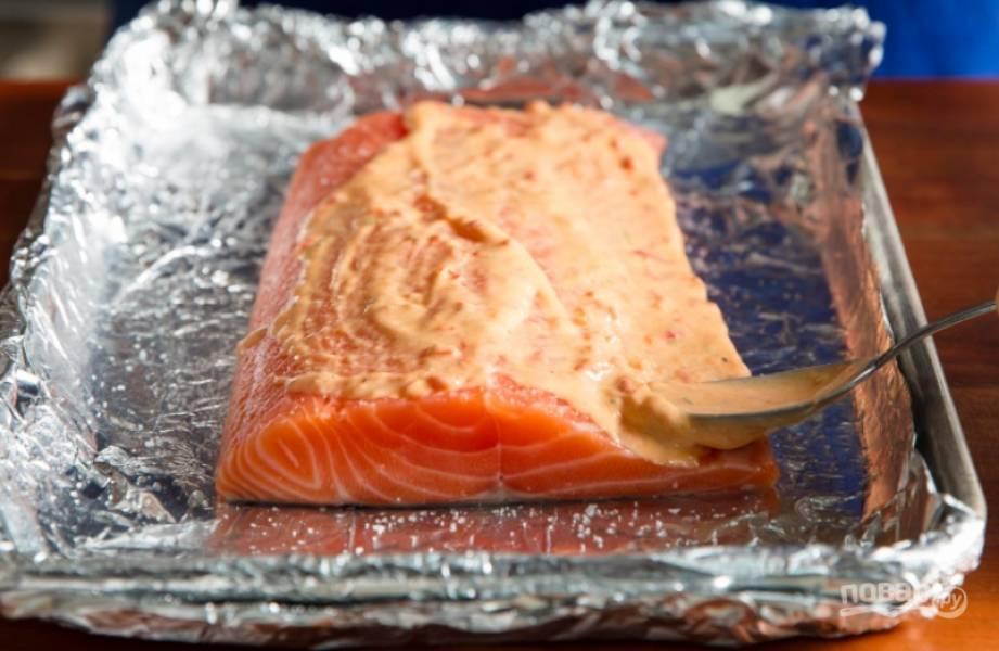 Посолите рыбу. Смешайте майонез, перец чили, сок и цедру лайма. Смажьте щедро таким соусом рыбку.