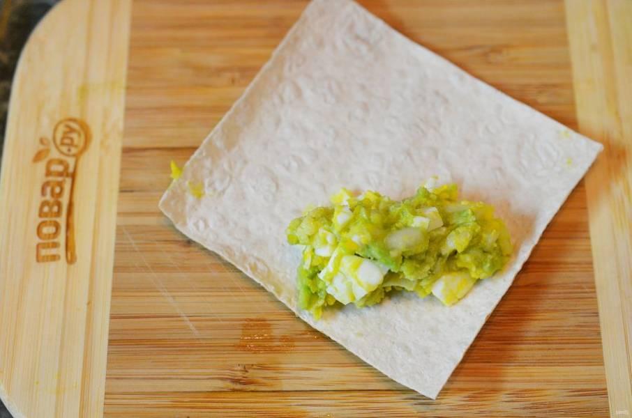 Вырезаем из лаваша квадрат. На уголок выложите начинку из авокадо.
