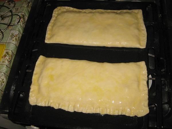 6. Форму для запекания или противень смазать слегка растительным маслом. Выложить пироги и смазать слегка взбитым яйцом. Отправить в предварительно разогретую духовку на 20-25 минут.