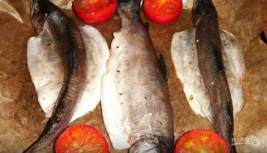 Маринованную рыбу переложите на противень, рядом с рыбой выложите половинки помидоров. Запекайте рыбу в разогретой духовке до 180 градусов до готовности в пределах 60 минут.