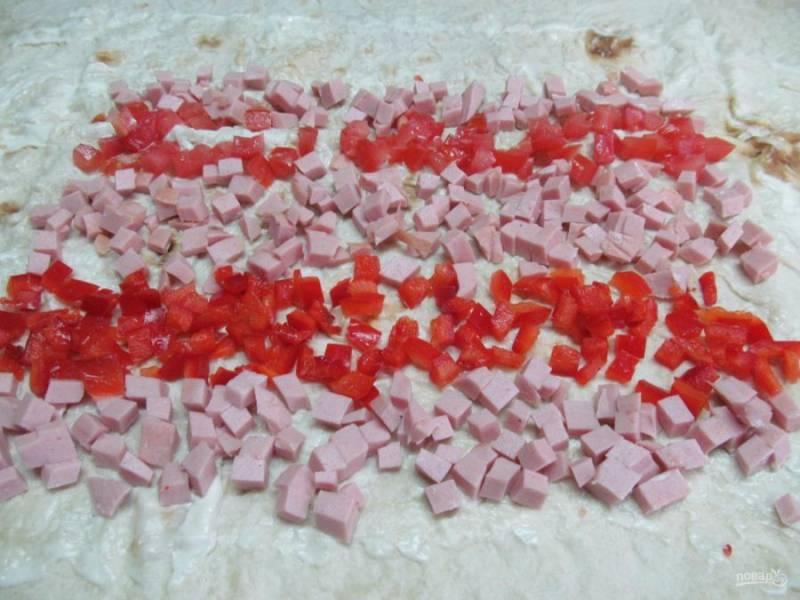 Мелким кубиком нарезаем колбасу и болгарский перец, выкладываем полосками на лаваш.