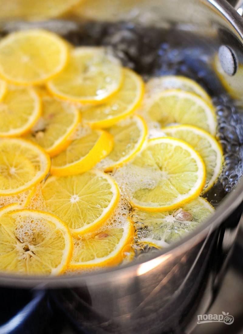 В глубокую кастрюлю налейте воды и доведите  до кипения. Убавьте огонь  и положите дольки лимонов на 1 минуту.
