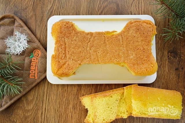 Обрежьте бисквит и придайте ему форму косточки. Разрежьте его вдоль на 2 коржа.