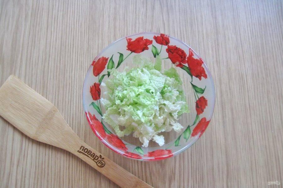 Пекинскую капусту нарежьте соломкой и выложите в салатник.