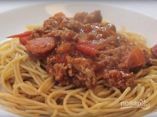Спагетти сварились, сливаем с них воду. Раскладываем спагетти по тарелкам и сверху выкладываем яркий мясной соус. Не забудьте попробовать соус и довести до вкуса, добавив соли или других специй.