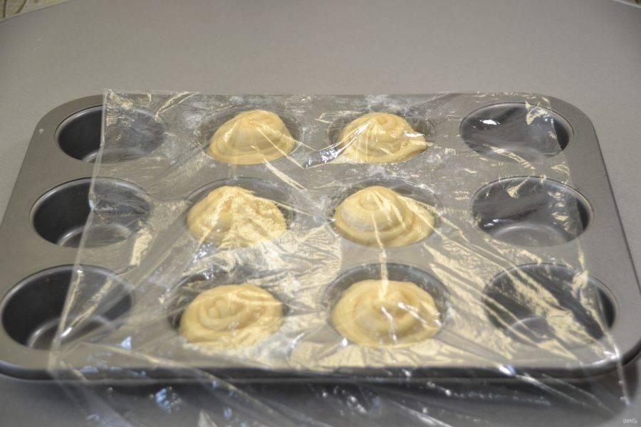 Уложите заготовки краффинов в подготовленную форму для выпечки. Я решила испечь только половину теста, а вторую половину оставить в холоде до следующего завтрака, убрав в пакет. Прикройте краффины плёнкой и оставьте при камнатной температуре для поднятия на 1 час.