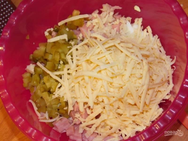 Натрите на крупной терке сыр и маринованные огурцы.