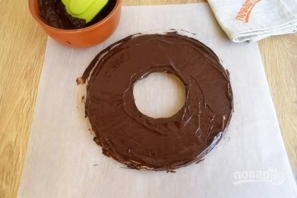 Шоколад поломайте на кусочки, растопите на водяной бане. Нанесите слой на остывшее песочное кольцо и поставьте в холодильник. Немного растопленного шоколада оставьте для покрытия слоя карамельной стружки.