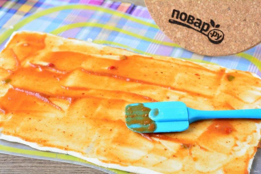 Размороженное слоеное тесто раскатайте, смажьте кетчупом.