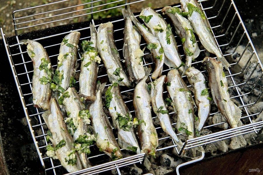 Выложите рыбу на решетку-гриль и жарьте на углях до готовности.