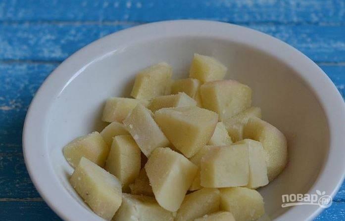 Картофель помойте и отварите в мундирах до полной готовности. Затем остудите его и снимите кожицу. Нарежьте картофель небольшими кубиками.