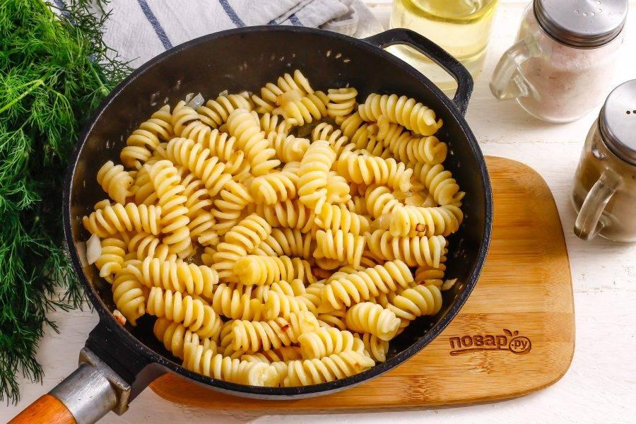 Слейте бульон с макарон и добавьте их в сковороду к обжаренному луку. Поджарьте содержимое емкости примерно 1-2 минуты.