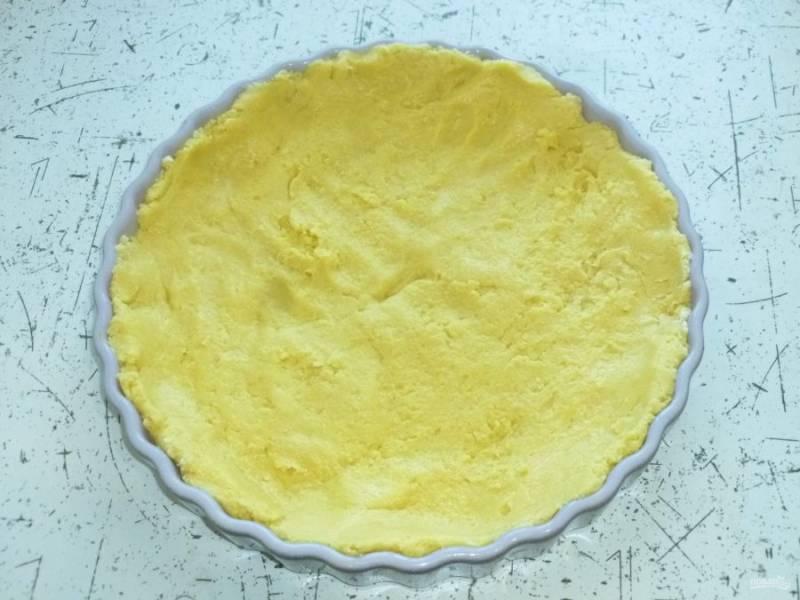 Выложите тесто в форму, для удобства можно смочить руки водой. Распределите тесто по дну и стенкам формы.
