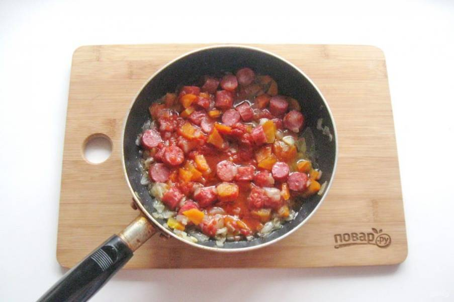 Перемешайте овощи с колбасками и тушите еще 5-7 минут.