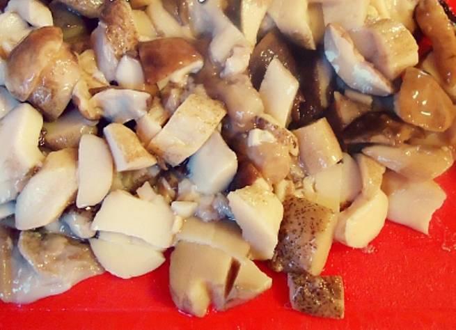 Помойте под проточной водой и нарежьте шампиньоны. Если вы используете другие грибы – их следует предварительно отварить.