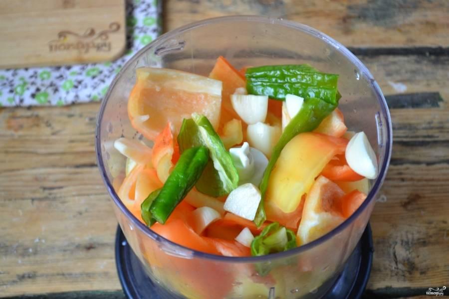 Все остальные овощи – сладкий и острый перец, чеснок – порежьте кусочками и сложите в чашу блендера. Измельчите все до состояния кашицы.