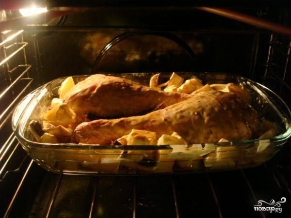 Когда мясо замариновалось, можно включать духовку для разогрева и подготовить картофель: почистите, помойте и нарежьте его крупными ломтиками.  Индейку достаньте из холодильника, переверните, чтобы опять сметанно-горчичный маринад распределился равномерно, выложите вокруг голеней нарезанный картофель и поставьте в разогретую духовку.