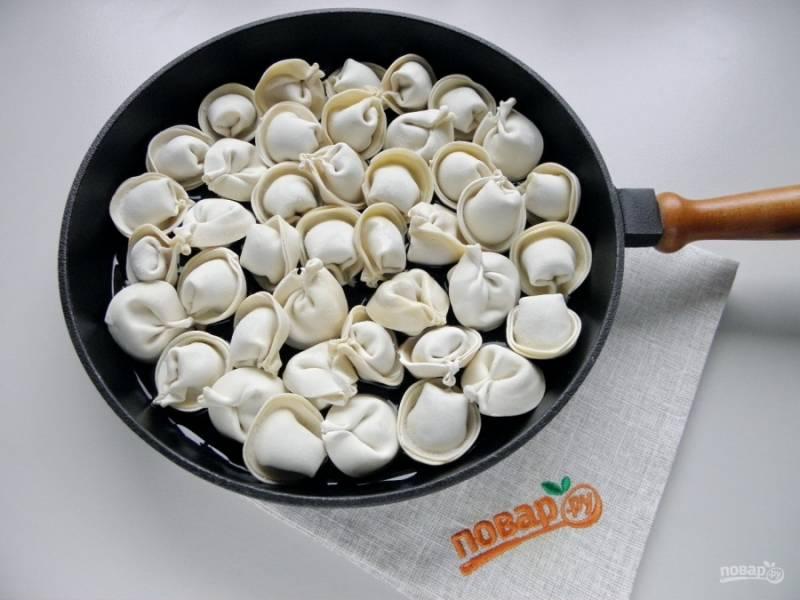 Разогрейте сковороду, влейте растительное масло, положите пельмени, залейте стаканом воды. Закройте крышкой сковороду и жарьте пельмени, периодически помешивая их лопаткой, в течение 10 минут.