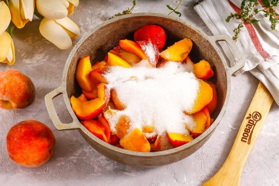 Нарежьте мякоть персиков ломтиками в казан или кастрюлю с антипригарным дном. Всыпьте сахарный песок. По желанию можете добавить немного лимонной кислоты или лимонного сока. Аккуратно перемешайте. Поместите емкость на плиту.