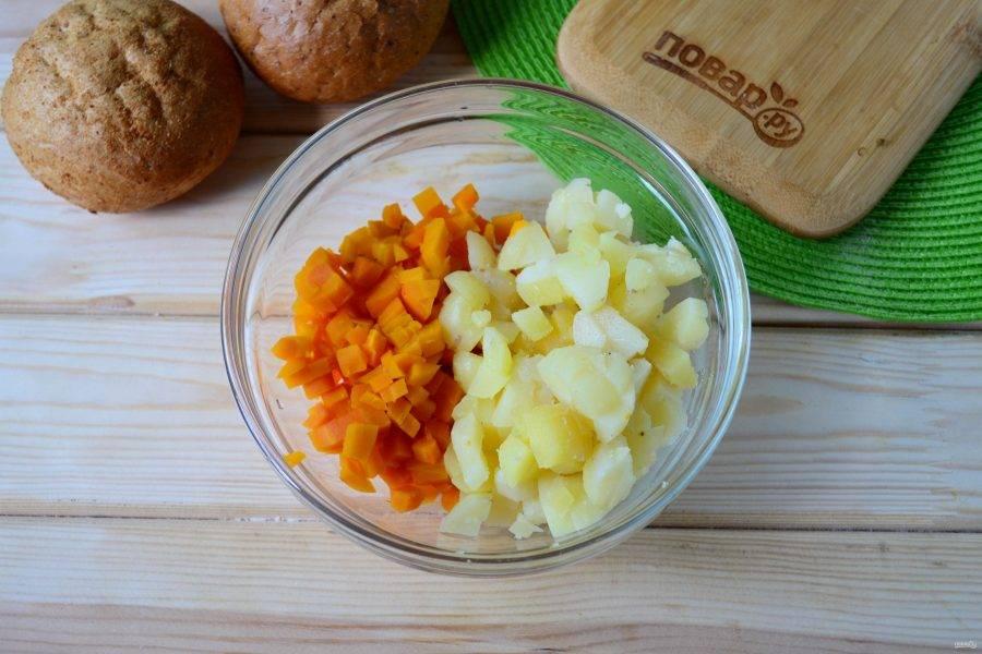 Вареную колбасу нарежьте мелкими кубиками, такими же кубиками нарежьте картофель и морковь.