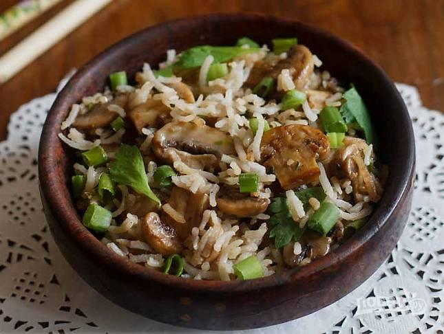 Горячие грибочки смешайте с рисом и добавьте соевый соус, хорошо все перемешайте.