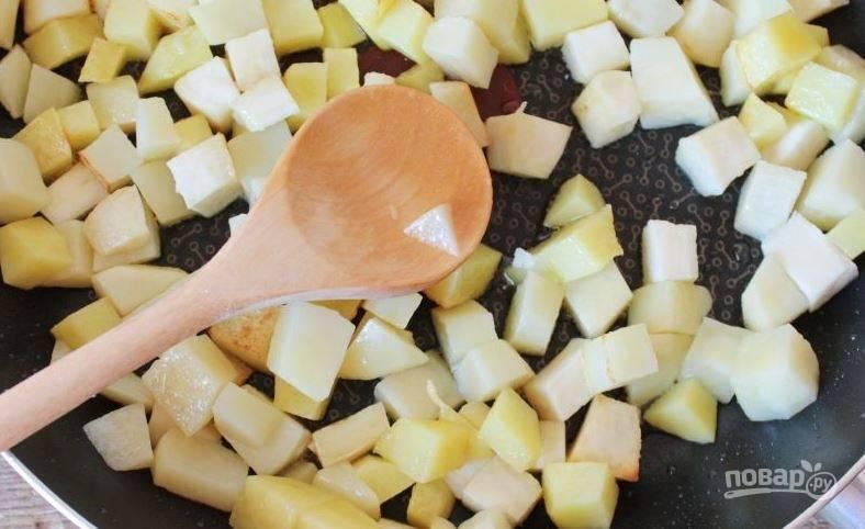 Поставьте на плиту сковороду и положите в нее сливочное масло. Пока сковорода разогревается, очистите и вымойте картофель и батат. Нарежьте клубни кубиками и обжарьте на сливочном масле до золотистой корочки.