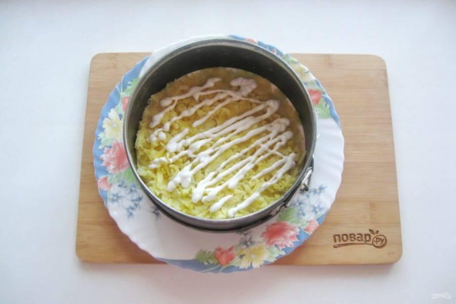 Картофель отварите, охладите, очистите и натрите на терке. Выложите на тарелку первым слоем. Покройте майонезом.