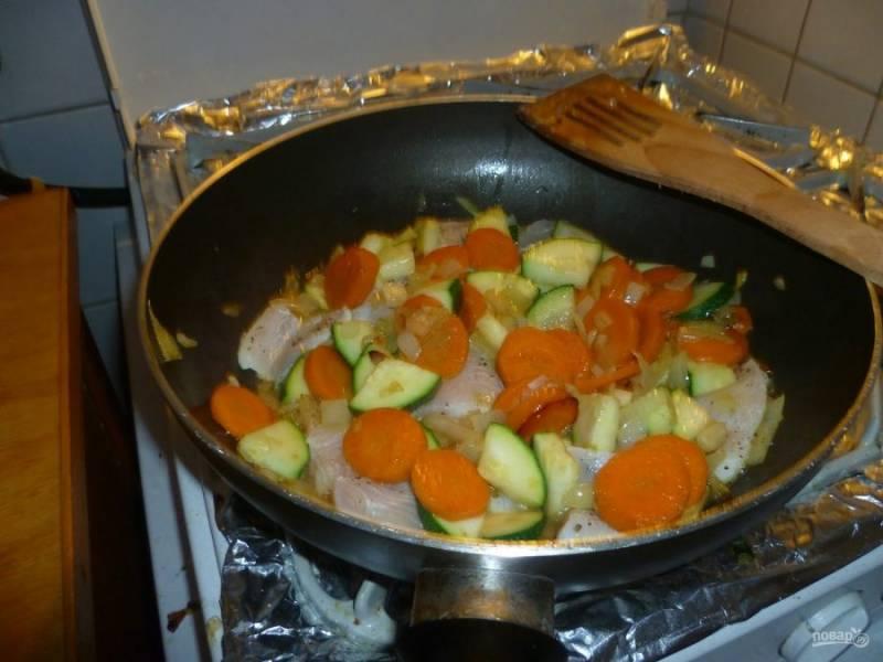 Когда морковь и цукини станут мягкими, добавьте в сковороду пангасиуса. Тушите блюдо до готовности.