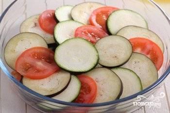 В жаропрочную форму уложите половину ингредиентов со сковороды. Затем поочерёдно одну часть нарезанных овощей. Вторую половину тушёных овощей и оставшиеся кружки.