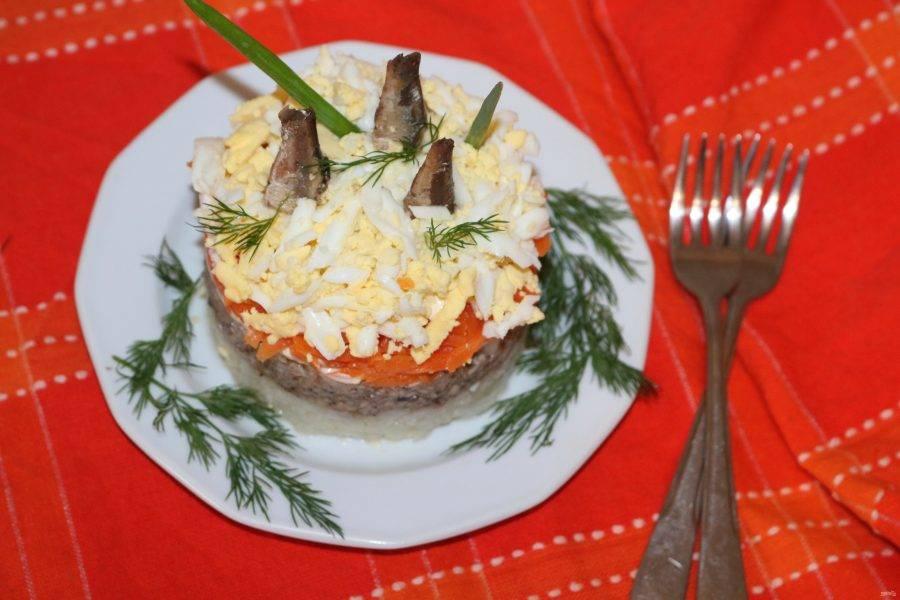 Украсьте салат зеленью и шпротными хвостиками.