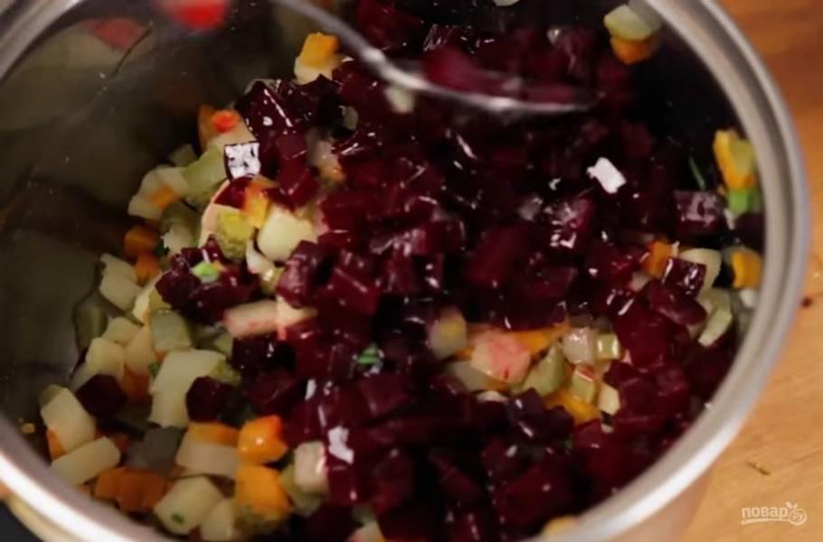3. Нарежьте мелкими кубиками огурцы и измельчите зелень, добавьте это все в кастрюлю с картофелем и морковью. Затем добавьте свеклу и зеленый горошек, посолите, перемешайте.