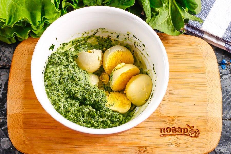 Аккуратно извлеките желтки и выложите в глубокую емкость. Туда же добавьте зеленый соус, и тщательно все перемешайте.