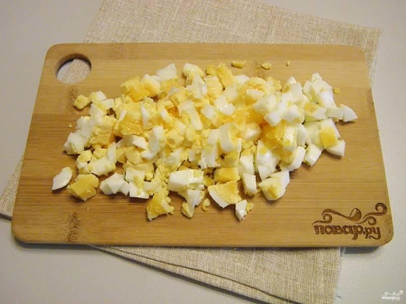 Порубите острым ножом яйца кубиками среднего размера.
