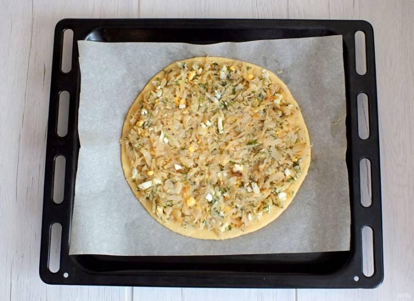 На противень постелите пергамент, переложите раскатанное тесто. Разложите подготовленную начинку. Включите духовку на 180 градусов.
