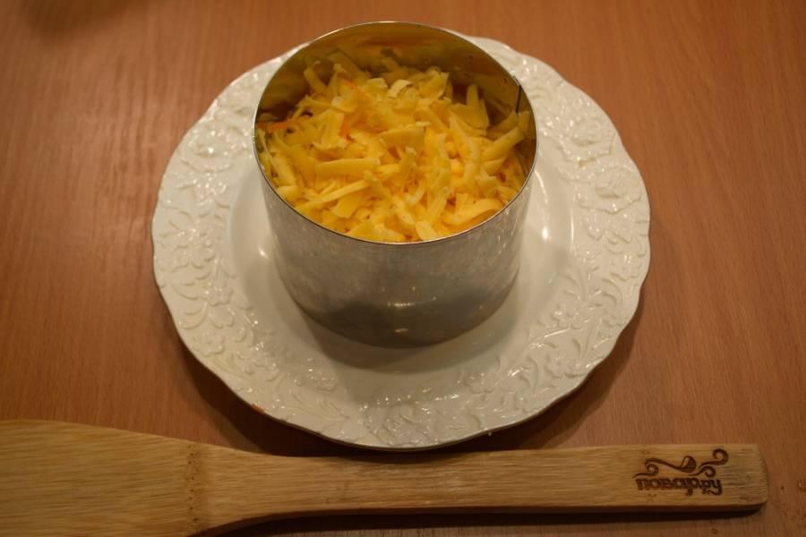 Смажьте слой моркови майонезом или сметаной. Теперь натрите на тёрке твёрдый сыр. Уложите ровно. Смажьте майонезом.